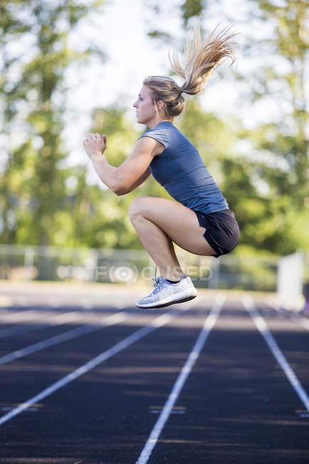 Жіночий бігун практикуючих стрибок присідання під час тренування трек, перш ніж запустити. — стокове фото