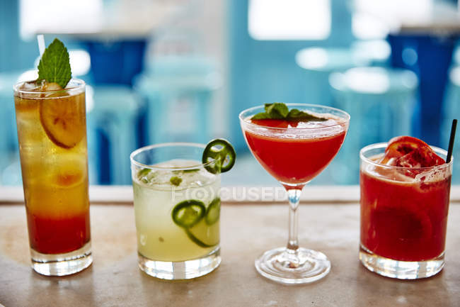 Lineup of four freshly poured colorful cocktails on bar counter — Stock Photo