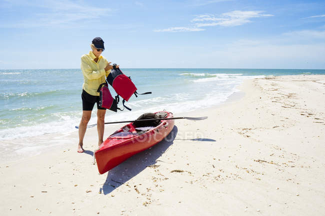 Woman putting on life vest beside kayak on beach — Stock Photo
