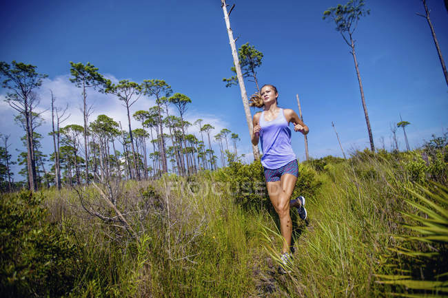 Young woman running on tall grass — Stock Photo