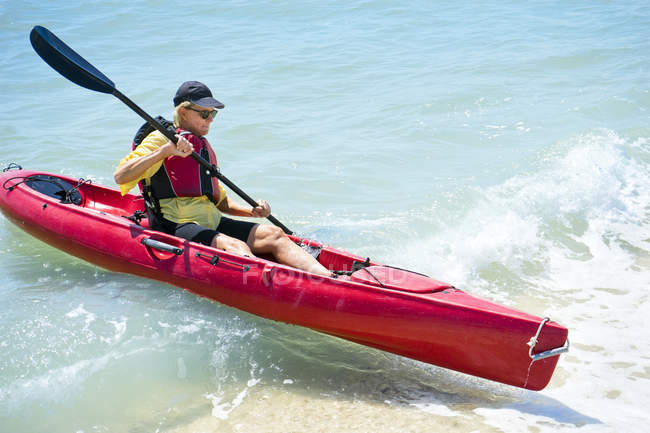 Side view of woman paddling in kayak on wave — Stock Photo
