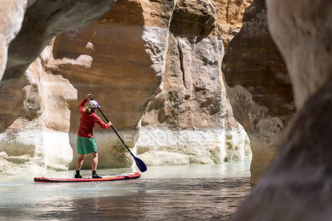 Side view of woman standing on paddleboard, Havasu River, Grand Canyon, Arizona — Stockfoto