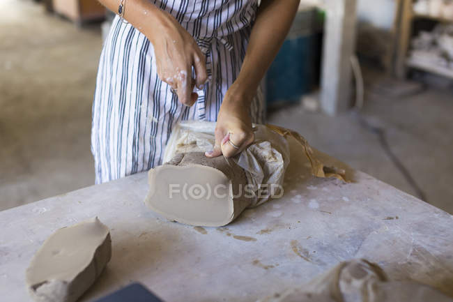 Close up of woman giving shape to clay in ceramic workshop — Stock Photo