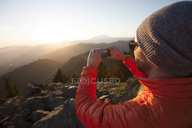A hiker uses his smartphone to take a a picture of the view from the summit of Sauk Mountain, Washington. — Stock Photo