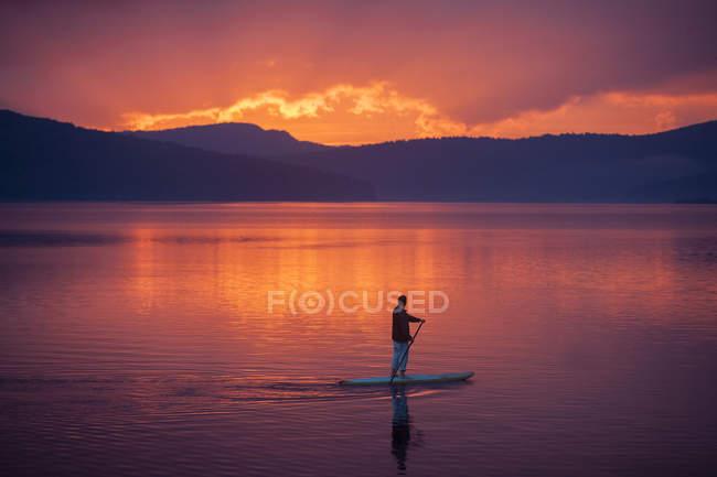 Людина весла інтернат під час заходу — стокове фото