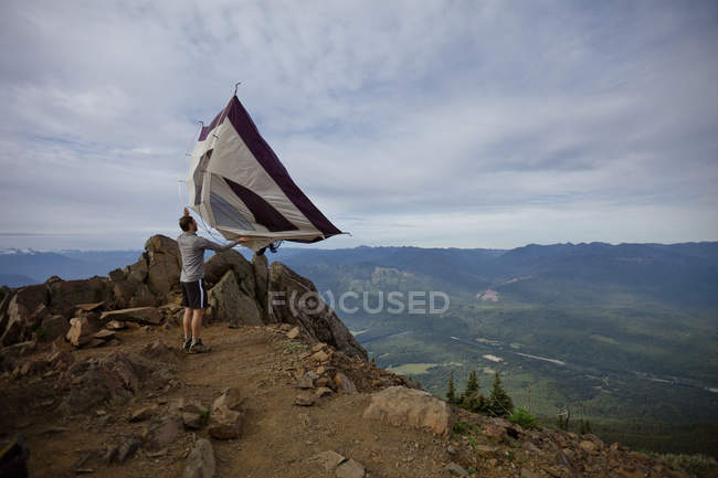 A hiker shakes his tent out after camping on the summit of Sauk Mountain, Washington. — Stock Photo