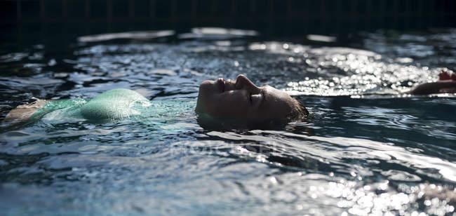 Retrato de mulher boiando na piscina — Fotografia de Stock