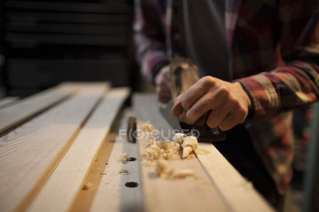 Arricciata legno trucioli vengono creati come carpentiere utilizza mano pialla a lavorare il pezzo di legno — Foto stock
