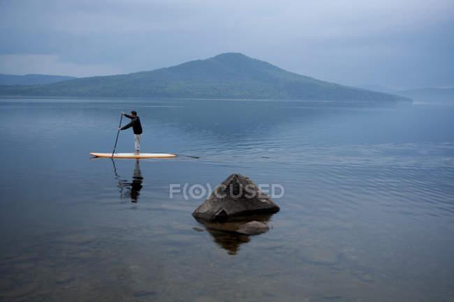 Людина весла інтернат проти гори — стокове фото