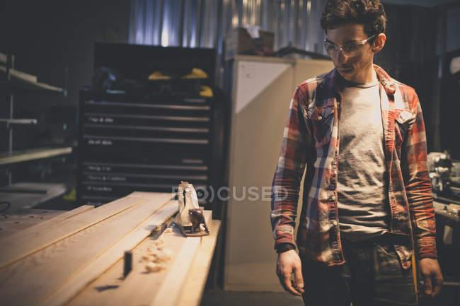 Ritratto di falegname pialla in Cerca a portata di mano sul banco di lavoro — Foto stock