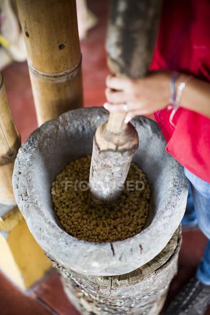 Молода жінка шліфувальних кави і використання старої техніки під час роботи — стокове фото