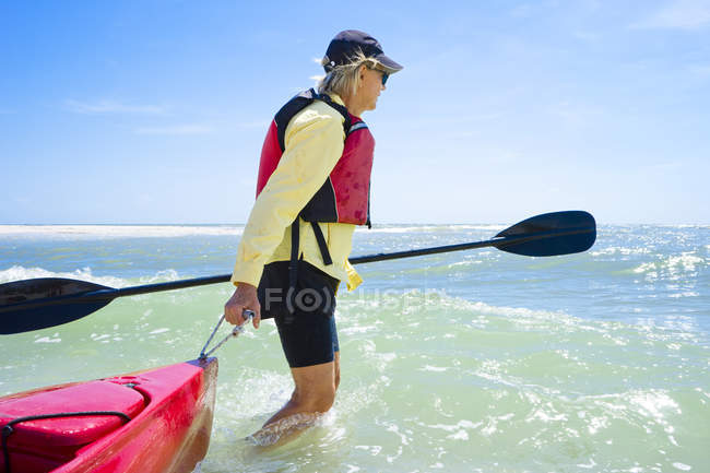 Side view of woman pulling kayak in surf — Stock Photo