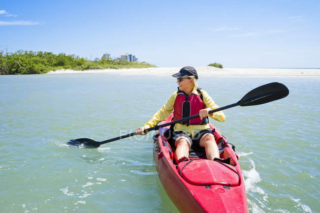 Mature woman paddling on kayak in calm water — Stock Photo