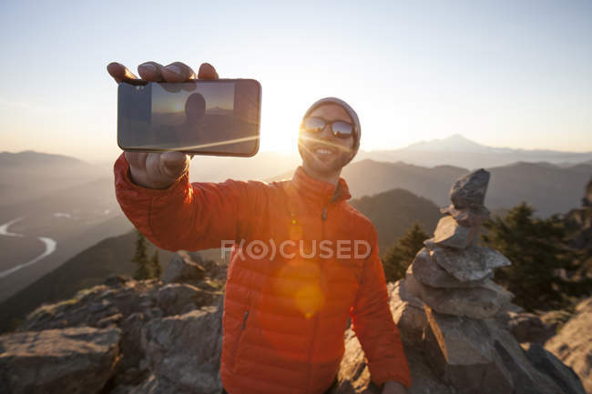 A man uses his smartphone to take a selfie at sunset from the summit of Sauk Mountain, Washington. — Stock Photo