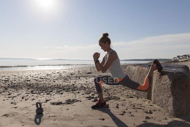 Mulher fazendo alongamento na praia — Fotografia de Stock