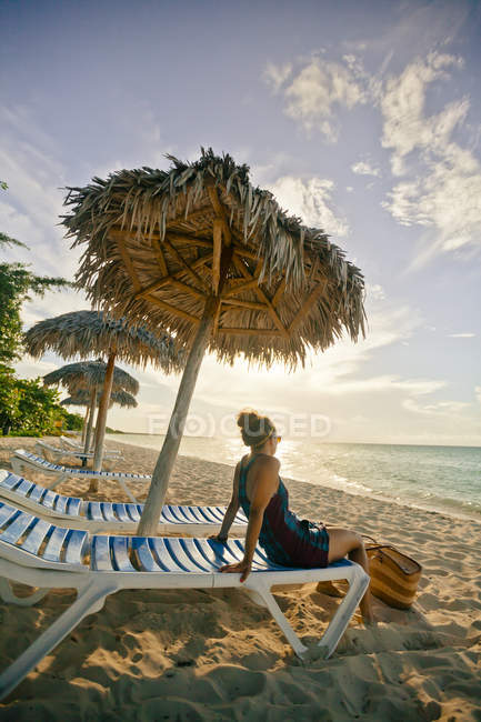A young woman relaxing on the beach under a beach umbrella in Cayo Coco, Cuba — Stock Photo