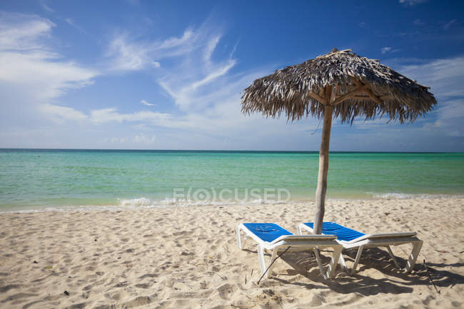 Palm leaf beach umbrella and two beach chairs on a sandy beach in Cayo Coco, Cuba — Stock Photo