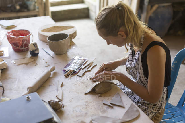 Side view of woman using craft knife on clay in ceramic workshop — Stock Photo