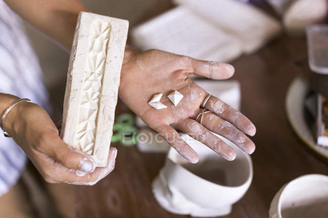 Close up of woman holding ceramic brick in hand — Stock Photo