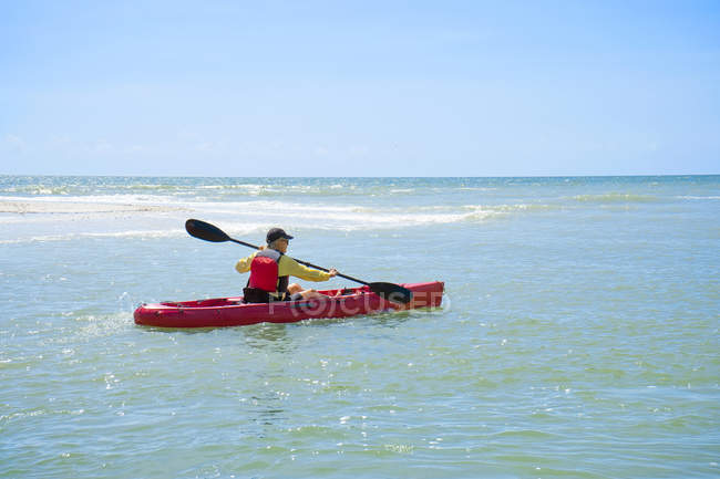 Rear view of woman kayaking in calm ocean — Stock Photo