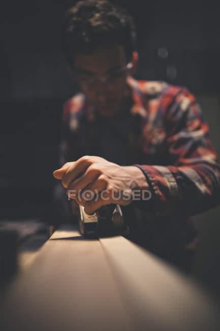 Carpentiere che lavora il pezzo di legno con pialla a mano — Foto stock