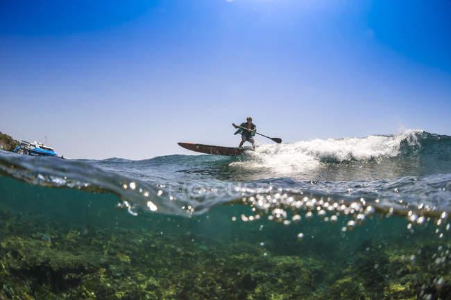 Vista distante de homem surfando em água tropical — Fotografia de Stock