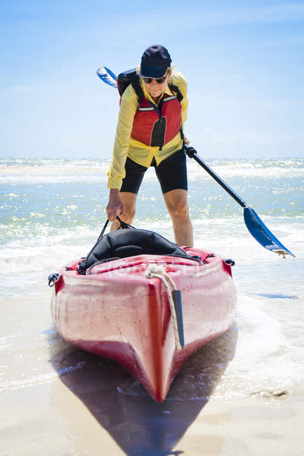 Mature woman pulling kayak into ocean — Stock Photo
