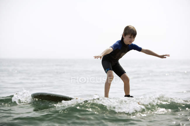 Young boy balancing on surfboard on wave — Stock Photo