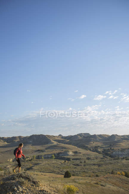 Side view of woman hiking in Theodore Roosevelt National Park, North Dakota. - foto de stock
