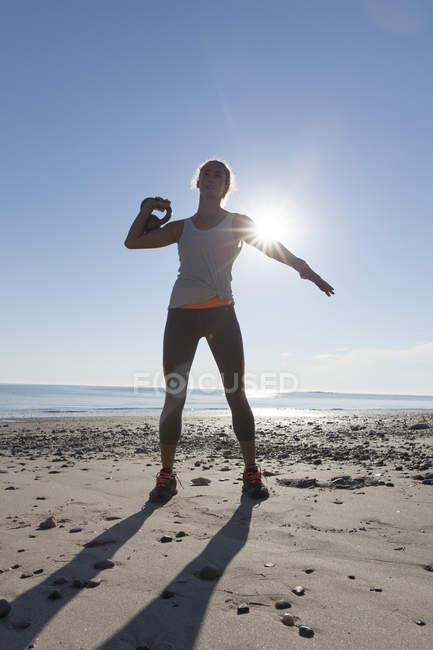Mulher fazendo exercício na praia com Kettlebell — Fotografia de Stock