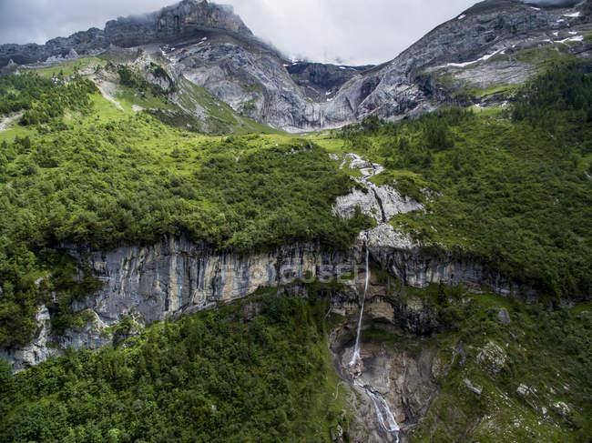 Alpine Landschaft mit einem Wasserfall über einen Felsvorsprung In Kanton Bern, Schweiz — Stockfoto