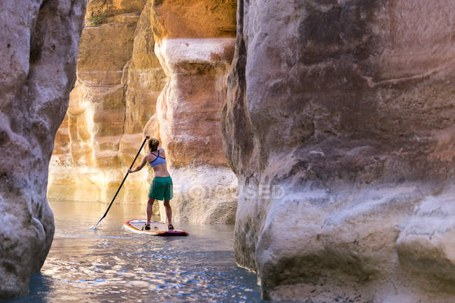 Woman floating on paddleboard between cliffs, Havasu River, Grand Canyon, Arizona — Stockfoto