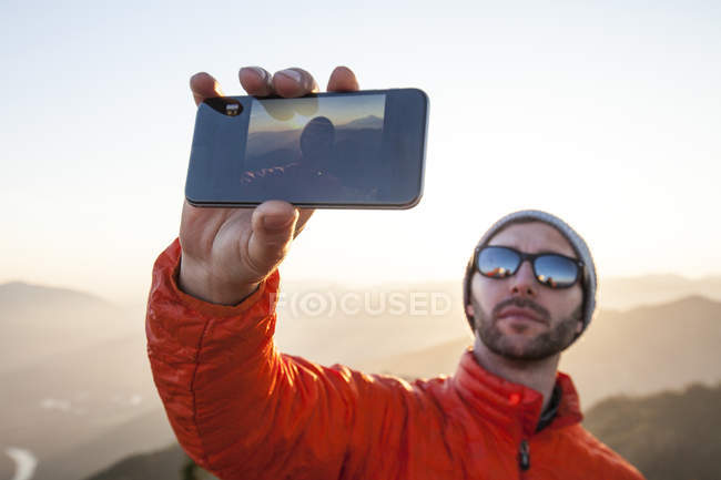 A hiker uses his smartphone to take a selfie while enjoying the outdoors. — Stock Photo