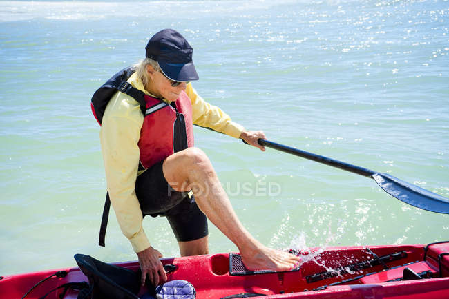 Woman holding oar and getting into kayak — Stock Photo