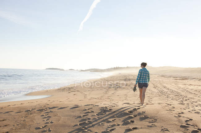 Rear view of woman walking along beach - foto de stock