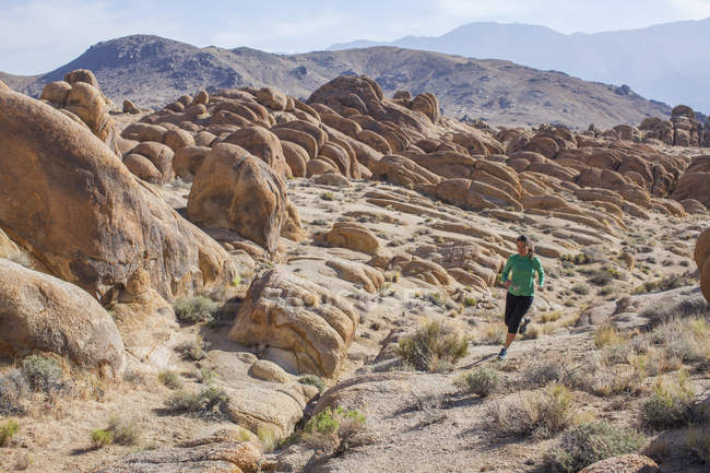 Woman Trail Running In Desert Landscape Of Alabama Hills National Recreation Area, California, Usa - foto de stock