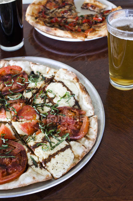 Close-up shot of pizzas and beer on table at restaurant — Stock Photo