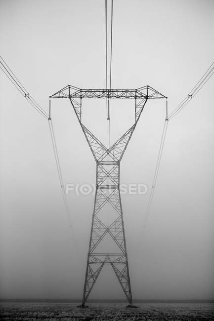 Selective focus of high voltage power lines and fog — Stock Photo