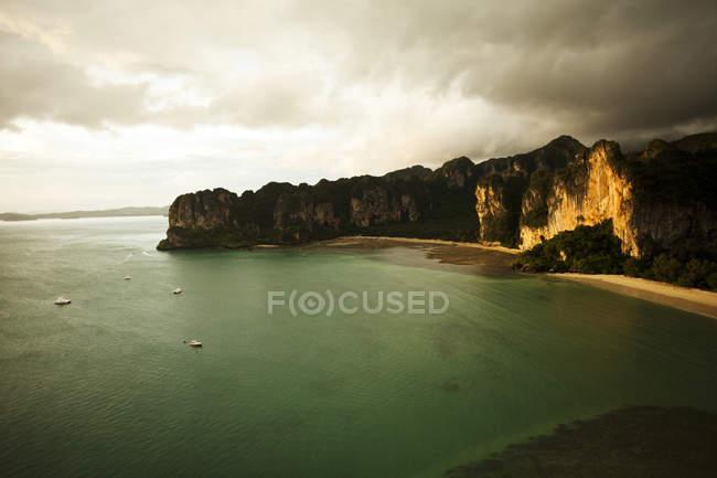 Аэрофотоснимок двух больших белых песчаных пляжей на закате, в окружении скал известняка и бирюзовой водой наполнен длиннохвостый лодки в Рейли, Таиланд — стоковое фото