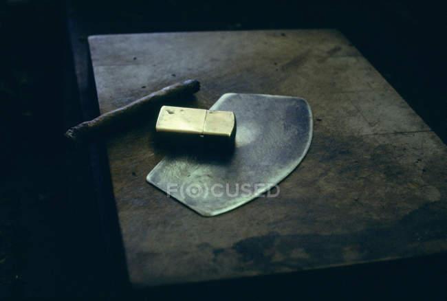 Nahaufnahme der angeordneten chavetta, Zigarre Rollen Messer, Feuerzeug und Zigarre auf Tischplatte — Stockfoto
