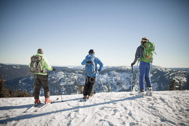 Three backcountry skiers prepare to descend the mountain. — стокове фото