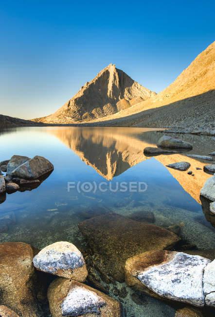 Sol iluminado rocas que reflejan en el agua del lago - foto de stock