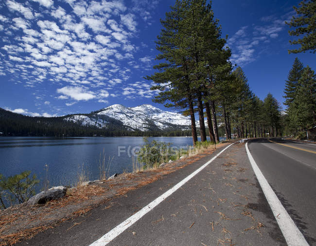 Road beside lake and snowcapped mountains under blue cloudy sky — Stock Photo