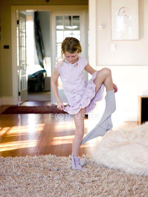 Jeune fille arrachant les collants à la salle de séjour, mettant l'accent sur le premier plan — Photo de stock