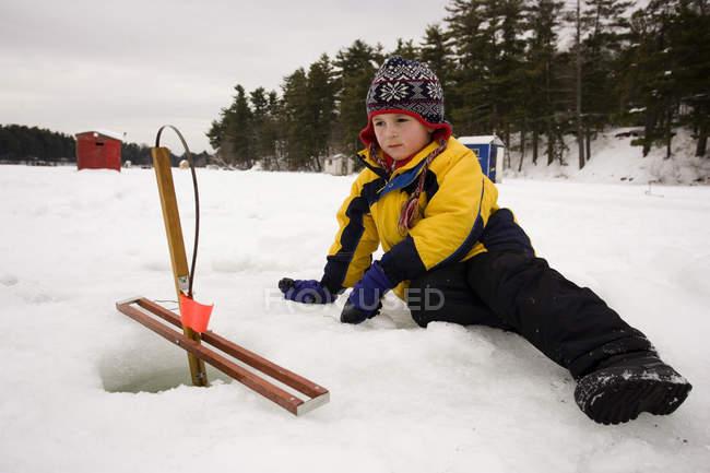 Garçon près de piège de glace pêche pour les poissons en attente si tout va bien — Photo de stock