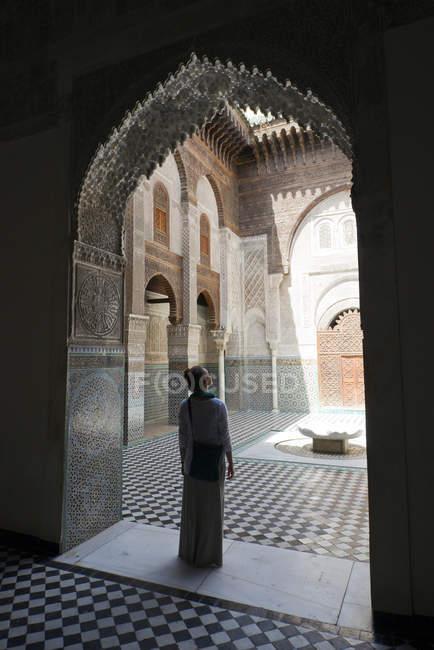 Frau stehend Silhouette in aufwendigen Tür im berühmten Koranschule Bou Inania in Fès el-Bali, Fes, Marokko — Stockfoto
