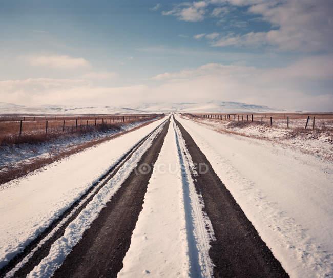 Solitaria carretera cubierta de nieve fresca en el rural de Alberta, Canadá. - foto de stock