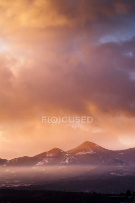 Céu nublado, montanhas na luz do nascer do sol quente — Fotografia de Stock
