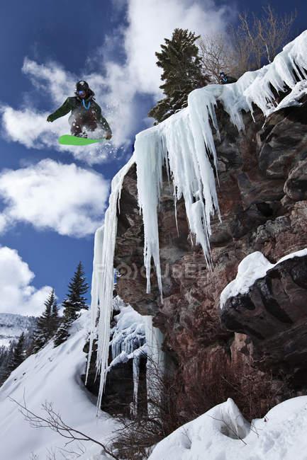 Snowboarder masculino pular penhasco da cascata de gelo em um dia ensolarado em Vail, Colorado — Fotografia de Stock