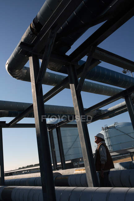 Worker in protective clothing checking lines against blue sky — Stock Photo